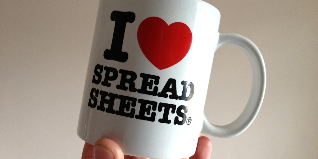 Someone holding a white the base of a mug that has 'I heart spreadsheets' printed on it.